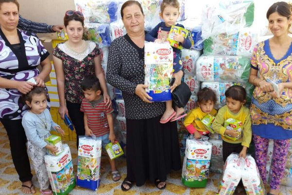 A group of women pose with their children after receiving their diaper supply.