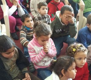Christian refugee children bow their heads in prayer during one of our Christmas for Refugee programs.