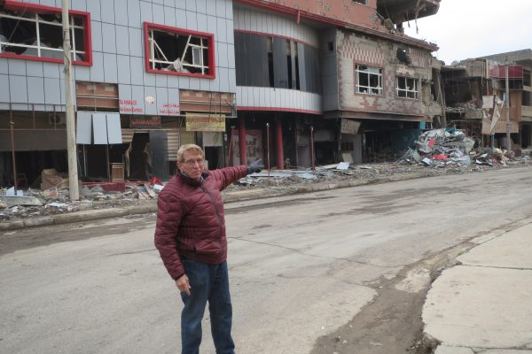 William J. Murray stands outside a building in Qaraqosh that had been destroyed by IS militants.